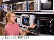 Купить «Positive female looking new microwave for kitchen in furniture store», фото № 30160589, снято 1 марта 2018 г. (c) Яков Филимонов / Фотобанк Лори
