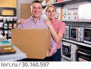 Купить «Happy young family with packed purchases in store», фото № 30160597, снято 1 марта 2018 г. (c) Яков Филимонов / Фотобанк Лори