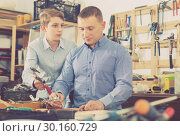 Купить «father and teen son working with wood plank in workshop», фото № 30160729, снято 17 мая 2017 г. (c) Яков Филимонов / Фотобанк Лори