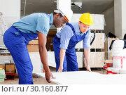 Купить «Two male builders working at indoors building site», фото № 30160877, снято 4 мая 2018 г. (c) Яков Филимонов / Фотобанк Лори
