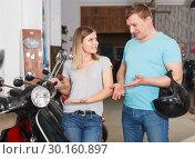 Купить «Glad man and girl is choosing modern motobikes», фото № 30160897, снято 8 мая 2018 г. (c) Яков Филимонов / Фотобанк Лори