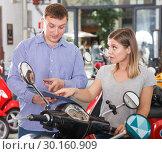 Купить «Couple is shopping and choosing new motobike», фото № 30160909, снято 8 мая 2018 г. (c) Яков Филимонов / Фотобанк Лори
