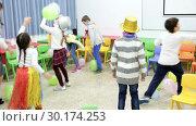 Купить «Happy kids and female teacher in funny hats and festive accessories playing together with colorful balloons in schoolroom», видеоролик № 30174253, снято 30 января 2019 г. (c) Яков Филимонов / Фотобанк Лори