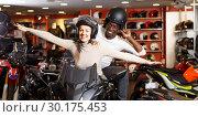 Купить «Cheerful young couple laughing sitting on bike», фото № 30175453, снято 16 января 2019 г. (c) Яков Филимонов / Фотобанк Лори