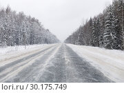 Купить «Winter road with ice on the asphalt, trees under snow during the winter frost», фото № 30175749, снято 25 июня 2019 г. (c) Mikhail Starodubov / Фотобанк Лори