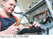 Купить «Shoemaker repair female spike shoe. Hammering tip on heel», фото № 30176049, снято 25 апреля 2018 г. (c) Дмитрий Калиновский / Фотобанк Лори