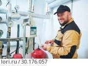 Купить «heating engineer or plumber inspector in boiler room taking readouts or adjusting meter», фото № 30176057, снято 5 октября 2018 г. (c) Дмитрий Калиновский / Фотобанк Лори
