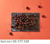 Delicious sweet cherry on a black stone board on a color background of the year 2019 Living Coral Pantone with place for text. Flat lay. Стоковое фото, фотограф Ярослав Данильченко / Фотобанк Лори