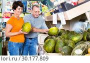 Купить «Adult male and female are choosing green melons in the store.», фото № 30177809, снято 22 октября 2017 г. (c) Яков Филимонов / Фотобанк Лори