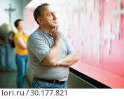 Portrait of thoughtful elderly man examining exposition in museum hall of applied arts. Стоковое фото, фотограф Яков Филимонов / Фотобанк Лори