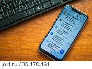 Купить «Смартфон с мошенническими смс сообщениями лежит на письменном столе рядом с компьютерной клавиатурой», эксклюзивное фото № 30178461, снято 23 февраля 2019 г. (c) Алёшина Оксана / Фотобанк Лори