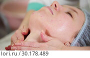 Купить «A face massage treatment in cosmetology clinic. Gently massaging the chin. Close up», видеоролик № 30178489, снято 22 марта 2019 г. (c) Константин Шишкин / Фотобанк Лори