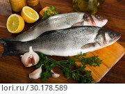 Купить «Cutting board with uncooked sea bass», фото № 30178589, снято 20 марта 2019 г. (c) Яков Филимонов / Фотобанк Лори