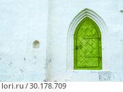 Купить «Architecture background. Medieval green metal forged door with arcade on the white stone wall», фото № 30178709, снято 19 августа 2016 г. (c) Зезелина Марина / Фотобанк Лори