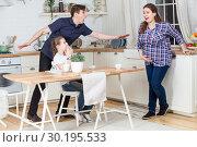 Внезапные схватки и беременной женщины во время завтрака с семьей. Стоковое фото, фотограф Кекяляйнен Андрей / Фотобанк Лори