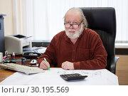 Купить «Пожилой мужчина инженер на рабочем месте делает пометки в чертежах, портрет», фото № 30195569, снято 22 февраля 2019 г. (c) Кекяляйнен Андрей / Фотобанк Лори