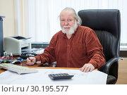 Купить «Пожилой мужчина сидит в кожаном офисном кресле в кабинете», фото № 30195577, снято 22 февраля 2019 г. (c) Кекяляйнен Андрей / Фотобанк Лори