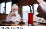 Купить «A young muslim women sitting and talking in modern cafe. A woman stir the drink with a straw», видеоролик № 30195621, снято 22 июля 2019 г. (c) Константин Шишкин / Фотобанк Лори