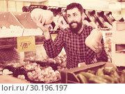 Купить «Young male seller offering pumpkins», фото № 30196197, снято 15 ноября 2016 г. (c) Яков Филимонов / Фотобанк Лори