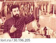 Купить «Young male customer examining sausages in butcher's shop», фото № 30196205, снято 16 ноября 2016 г. (c) Яков Филимонов / Фотобанк Лори