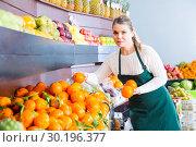 Купить «Glad female in apron selling fresh oranges», фото № 30196377, снято 18 июля 2019 г. (c) Яков Филимонов / Фотобанк Лори