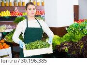 Купить «Salesgirl offering green beans», фото № 30196385, снято 31 января 2019 г. (c) Яков Филимонов / Фотобанк Лори