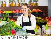 Купить «Salesgirl arranging greens», фото № 30196389, снято 31 января 2019 г. (c) Яков Филимонов / Фотобанк Лори
