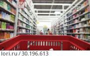 Купить «Grocery Cart Rolls Along Rows With Blurry Children's Toys», видеоролик № 30196613, снято 3 октября 2018 г. (c) Pavel Biryukov / Фотобанк Лори