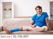 Купить «Leg injured young man on the sofa», фото № 30196897, снято 19 сентября 2018 г. (c) Elnur / Фотобанк Лори