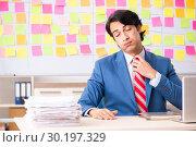 Купить «Young handsome employee with many conflicting priorities», фото № 30197329, снято 16 октября 2018 г. (c) Elnur / Фотобанк Лори