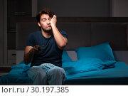 Купить «Man watching tv at night in bed», фото № 30197385, снято 18 сентября 2018 г. (c) Elnur / Фотобанк Лори