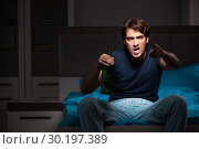 Купить «Man drinking in the bed under stress», фото № 30197389, снято 18 сентября 2018 г. (c) Elnur / Фотобанк Лори