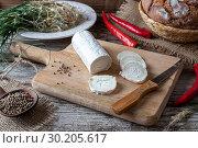 Купить «Cutting goat cheese before pickling it with crow garlic, hot peppers and coriander seeds.», фото № 30205617, снято 19 февраля 2019 г. (c) easy Fotostock / Фотобанк Лори