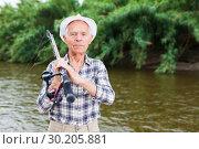 Mature fisherman with rod at riverside. Стоковое фото, фотограф Яков Филимонов / Фотобанк Лори