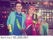 Купить «Sporty couple in sportwear is demonstraiting modern racket and balls for padel», фото № 30206061, снято 7 февраля 2018 г. (c) Яков Филимонов / Фотобанк Лори