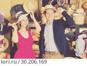 Купить «positive young female and man choosing hats in the store», фото № 30206169, снято 2 мая 2017 г. (c) Яков Филимонов / Фотобанк Лори