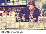 Купить «Man standing near the counter and selling details for plumbing in hardware shop», фото № 30206201, снято 4 мая 2017 г. (c) Яков Филимонов / Фотобанк Лори