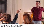 Купить «happy friends playing charades at home in evening», видеоролик № 30206841, снято 12 января 2019 г. (c) Syda Productions / Фотобанк Лори