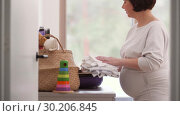 Купить «pregnant woman packing bag for maternity hospital», видеоролик № 30206845, снято 19 февраля 2019 г. (c) Syda Productions / Фотобанк Лори