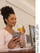 Купить «Beautiful woman having orange juice while using mobile phone at home», фото № 30207281, снято 7 ноября 2018 г. (c) Wavebreak Media / Фотобанк Лори