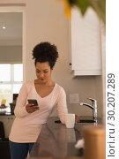 Купить «Woman having coffee while using mobile phone in kitchen», фото № 30207289, снято 7 ноября 2018 г. (c) Wavebreak Media / Фотобанк Лори