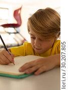 Купить «Boy drawing sketch on notebook at desk in a classroom», фото № 30207805, снято 10 ноября 2018 г. (c) Wavebreak Media / Фотобанк Лори