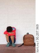 Купить «Sad schoolboy sitting alone on floor in corridor», фото № 30207969, снято 17 ноября 2018 г. (c) Wavebreak Media / Фотобанк Лори
