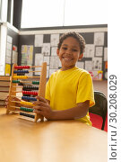 Купить «Happy schoolboy with abacus looking at camera in a classroom», фото № 30208029, снято 17 ноября 2018 г. (c) Wavebreak Media / Фотобанк Лори