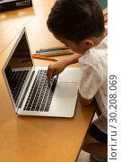 Купить «Schoolboy using laptop at table in a classroom», фото № 30208069, снято 17 ноября 2018 г. (c) Wavebreak Media / Фотобанк Лори
