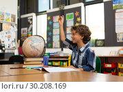 Купить «Schoolboy raising his hand at desk in the classroom», фото № 30208169, снято 17 ноября 2018 г. (c) Wavebreak Media / Фотобанк Лори