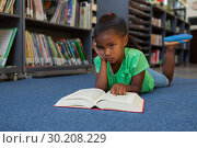 Купить «Schoolgirl reading a book in the library», фото № 30208229, снято 17 ноября 2018 г. (c) Wavebreak Media / Фотобанк Лори