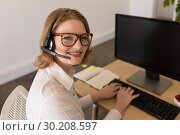Купить «Female executive in headset smiling in office», фото № 30208597, снято 18 ноября 2018 г. (c) Wavebreak Media / Фотобанк Лори