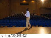 Купить « Businessman practicing and learning script while walking in the auditorium», фото № 30208621, снято 15 ноября 2018 г. (c) Wavebreak Media / Фотобанк Лори