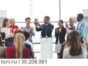 Купить «Businessman holding award at podium with colleagues in a business seminar», фото № 30208981, снято 21 ноября 2018 г. (c) Wavebreak Media / Фотобанк Лори